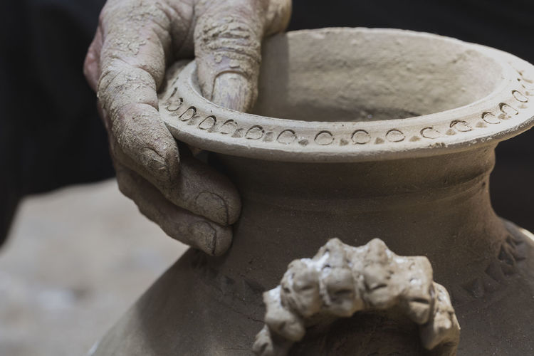 Cropped hand of potter holding earthenware in workshop