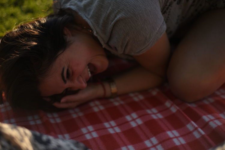 Smiling woman lying on picnic blanket