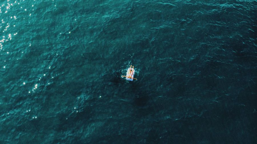 Aerial view of woman on inflatable raft in sea