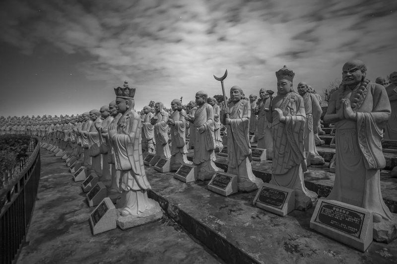 Various statues in row against sky