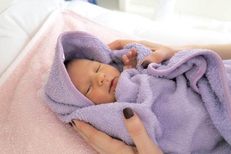 Baby girl sleeping on bed at home