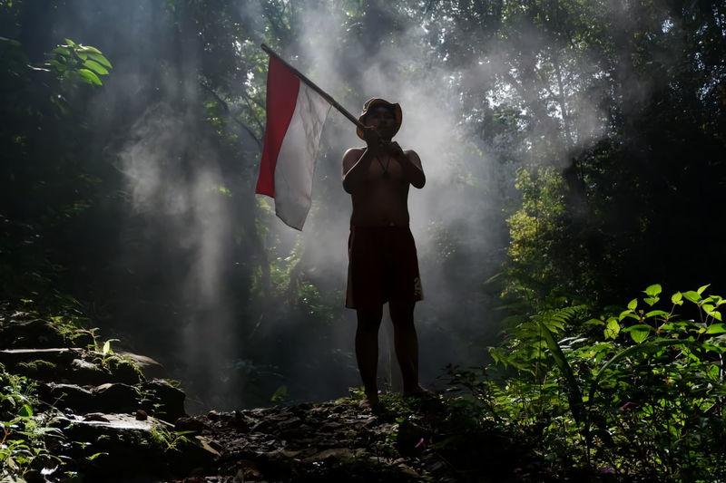 Full length of man holding flag standing against trees in forest