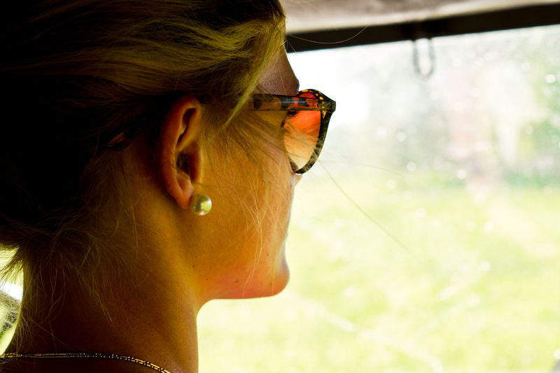Rear View Of Young Woman Looking Through Wet Windshield While Traveling In Car