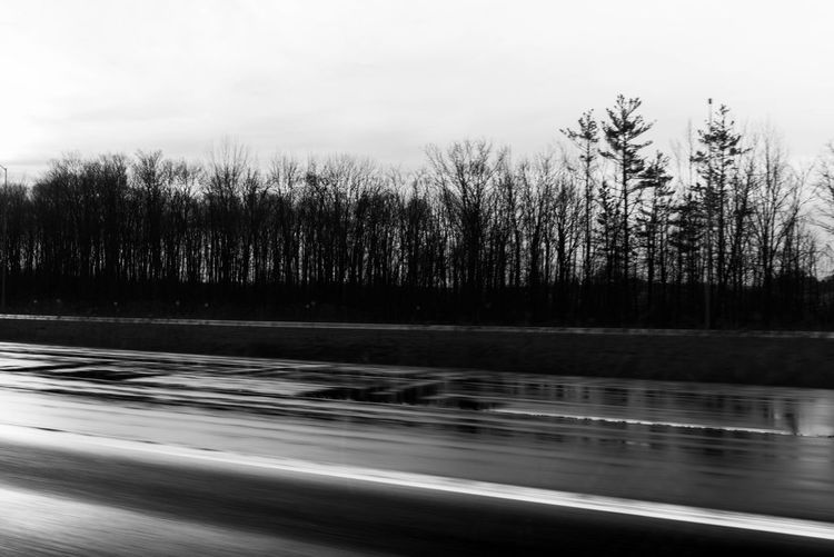 Blurred motion of road by trees against sky