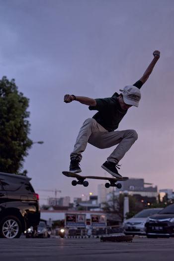 Full length of man jumping with skateboard on street against sky
