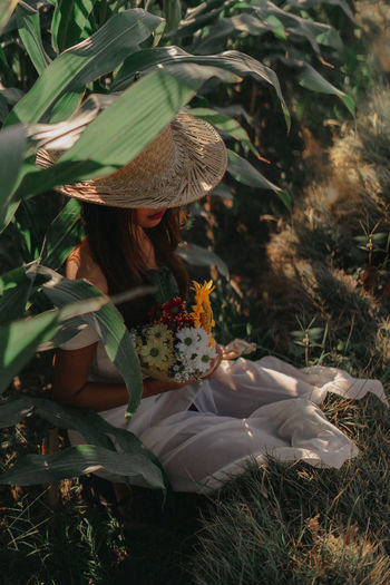 Woman holding flowers on field