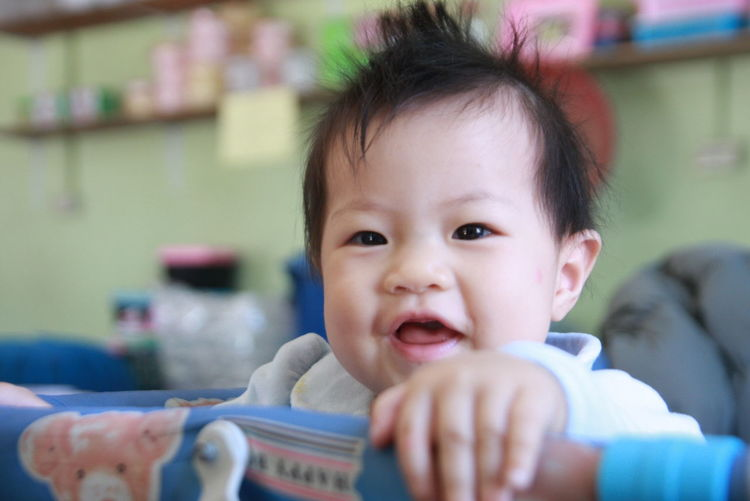 Close-Up Portrait Of Cute Baby Girl In Crib At Home