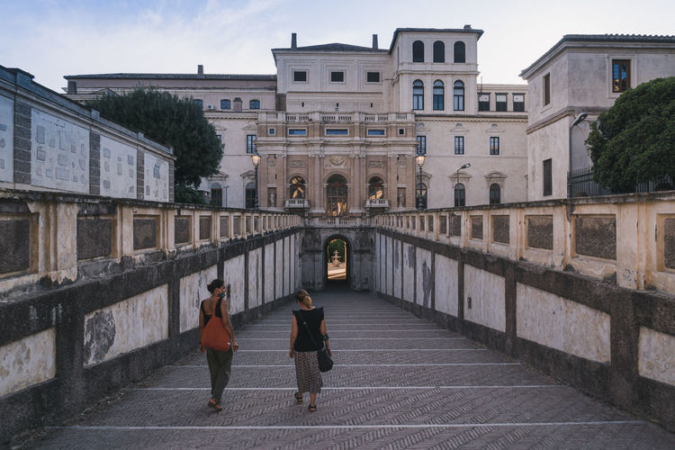 Rear view of people walking on historic building