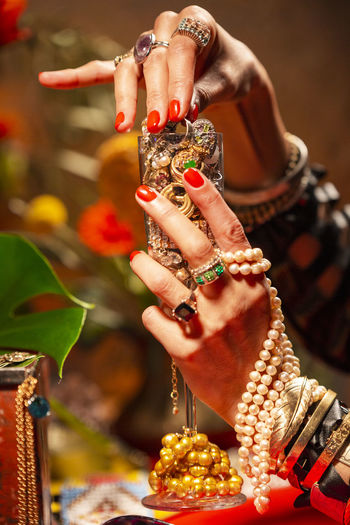 Gestures of a woman with jewelry, pearls, fruits and flowers. Abundance Wealth Celebration Art And Craft Mood Jewelry Gold Pearls Gesture Luxury Hand Human Hand Bracelet One Person Human Body Part Focus On Foreground Close-up Holding Adult Women Real People Ring Bangle Human Finger Indoors  Finger Creativity Nail