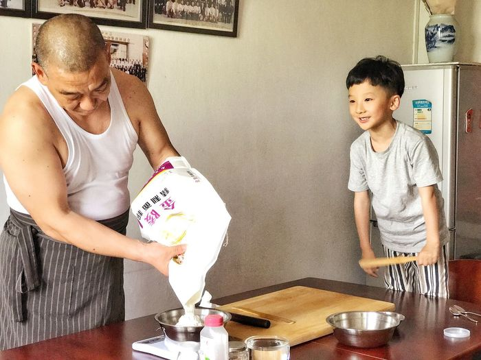 Love Handmade,Grandpa and boy. Can u guess what they are doing?ah,making BaoBao. Two People Child Indoors  Togetherness Childhood Table Domestic Life Standing Girls People Domestic Room Smiling Day Adult Live For The Story