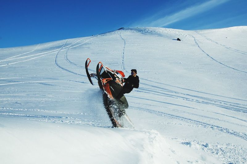 Snowmobile rider playing on deep snow