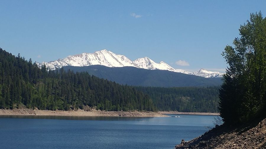 Scenic view of hungry horse reservoir by snowcapped mountains by against sky