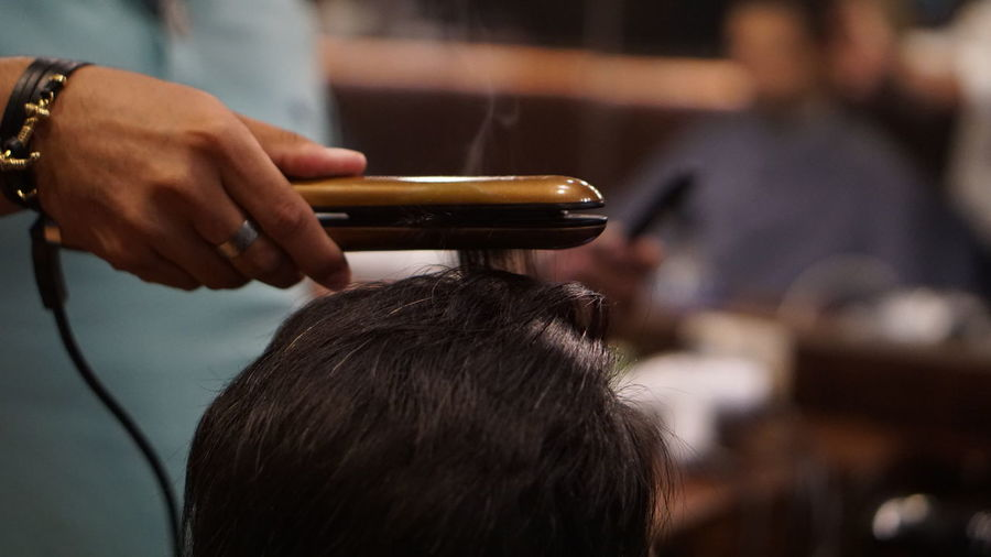 Close-up of hairdresser straightening hair