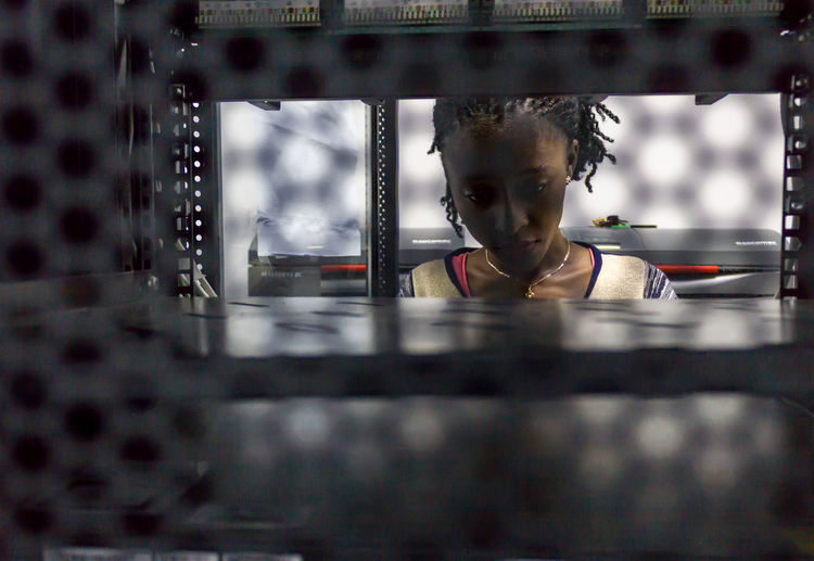 Young woman seen through metal grate