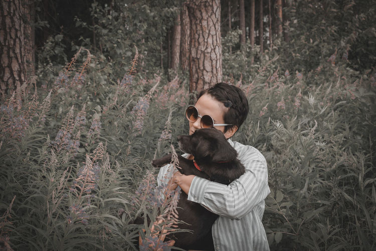 Young woman with dog in forest