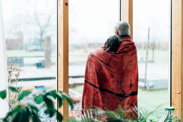 Back view of a senior couple at home wrapped in a blanket while looking outside from a big window