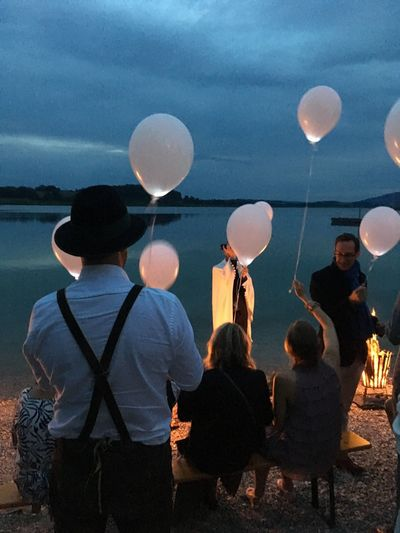 celebrating Twilight Lake Lederhose Balloons EyeEm Selects Women Real People Group Of People Rear View Adult Men Sky Togetherness Leisure Activity People Nature Group Decoration Outdoors Crowd