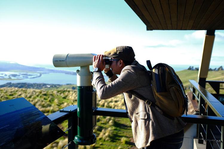 Man Looking Through Coin-Operated Binoculars