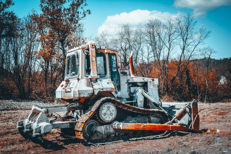 Abandoned bulldozer on field against sky
