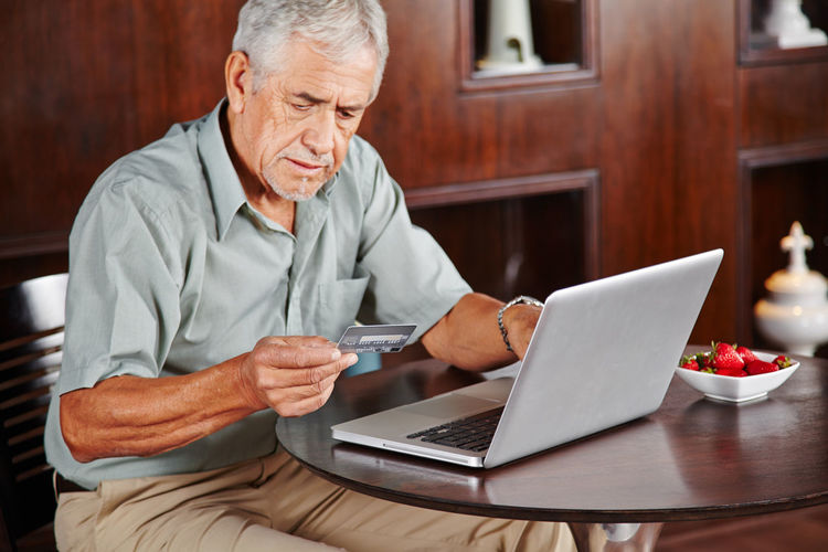 High angle view of senior man using credit card sitting by laptop at home