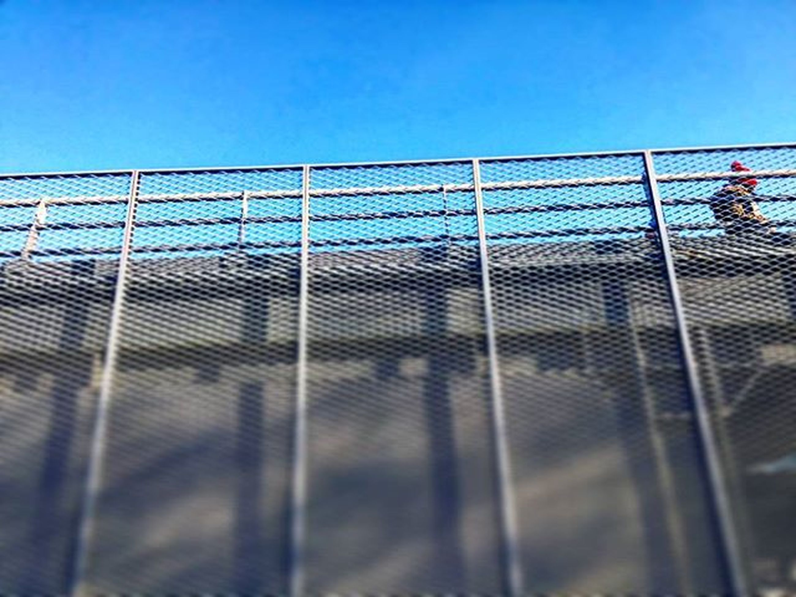 clear sky, blue, railing, copy space, built structure, architecture, men, sunlight, lifestyles, walking, shadow, building exterior, leisure activity, bridge - man made structure, outdoors, city, person, transportation, day