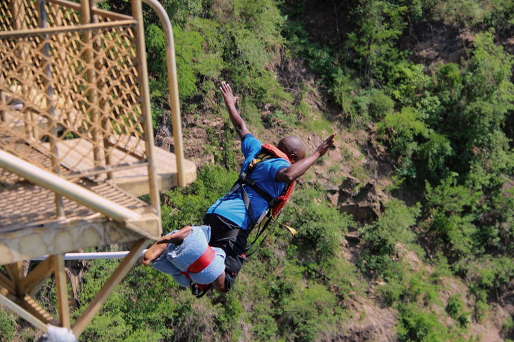 High angle view of man bungee jumping over trees in forest