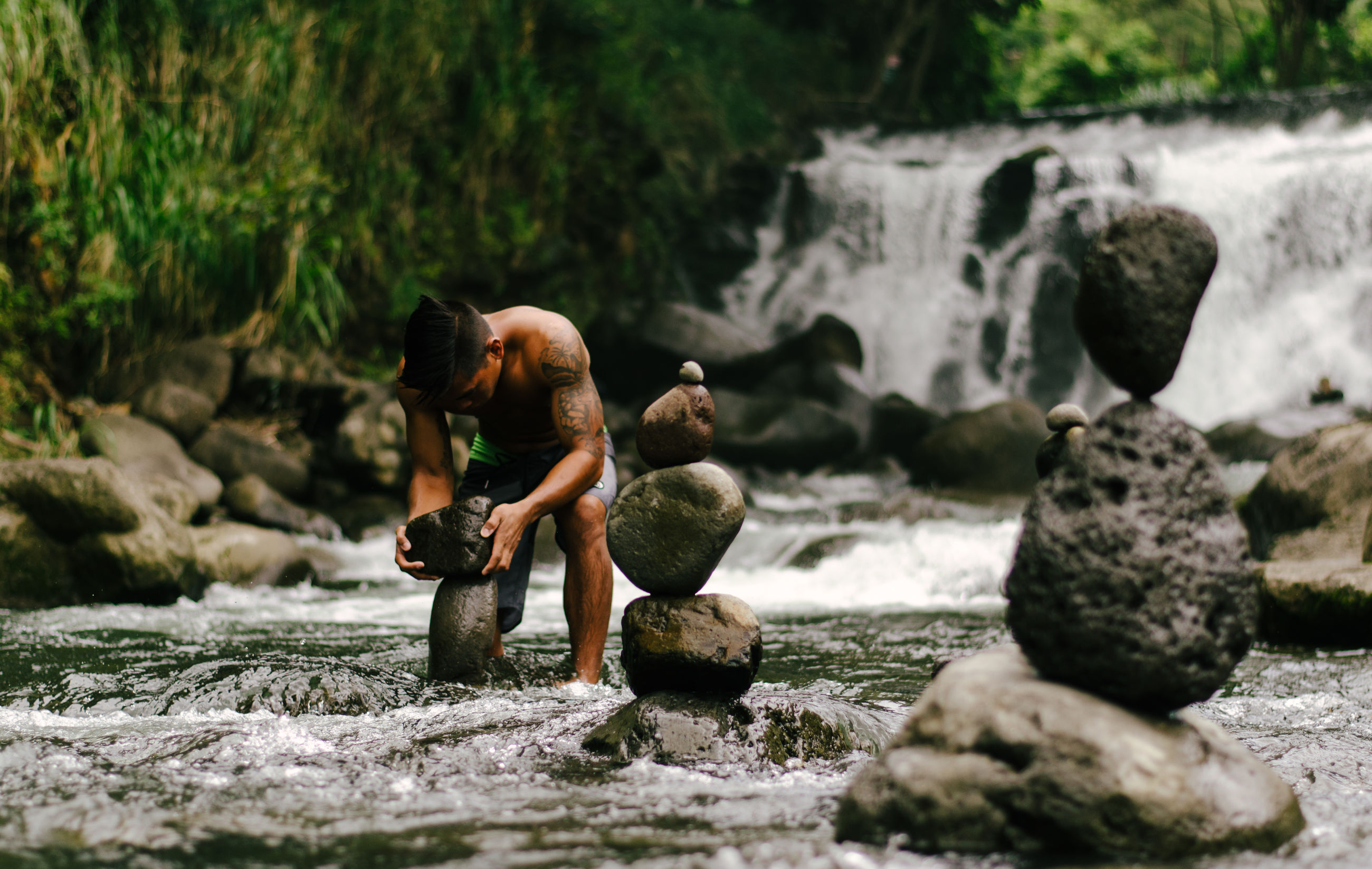 rock - object, leisure activity, lifestyles, water, men, full length, rear view, person, rock, togetherness, stone - object, childhood, casual clothing, focus on foreground, nature, boys, balance