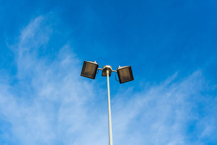 Low Angle View Sky Blue Cloud - Sky No People Outdoors Lighting Equipment Nature Day Copy Space Street Light Beauty In Nature Pole Street Sunlight White Color Electricity  Electric Light Tall - High Technology Directly Below Power Lamp Electricity