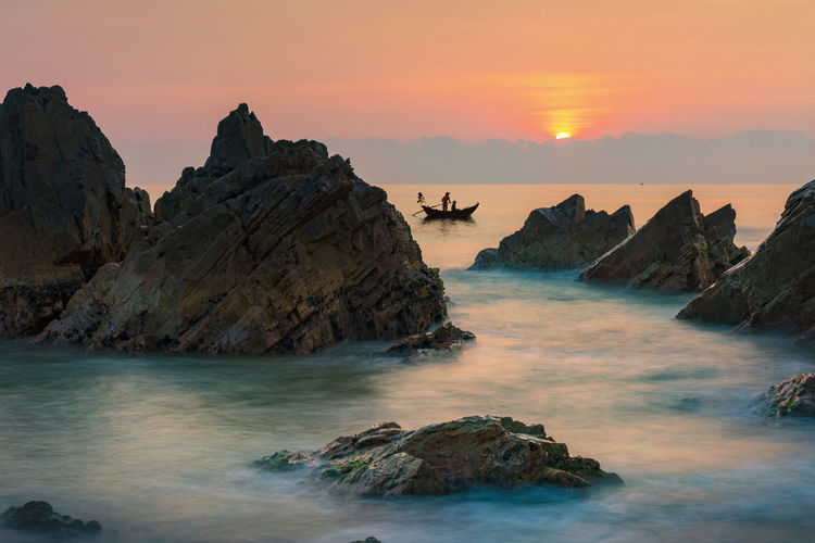 Photo taken at Da Nhay beach, Bo Trach district, Quang Binh province, Vietnam; Sea wave exposure long time Beach Beauty In Nature Eroded Horizon Over Water Idyllic Land Motion Nature No People Orange Color Rock Rock - Object Rock Formation Rocky Coastline Scenics - Nature Sea Sky Solid Stack Rock Sunset Tranquil Scene Tranquility Water Waterfront