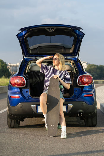 Rear view of woman standing in car