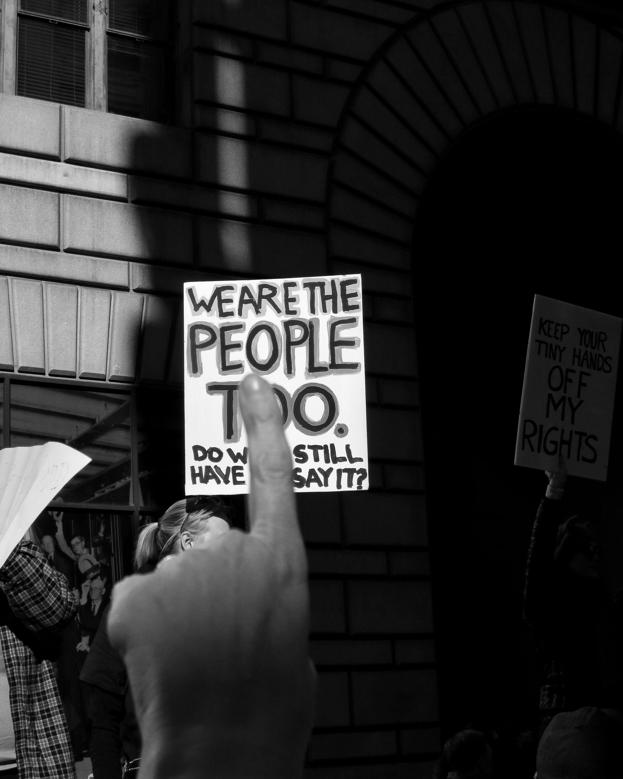 text, western script, communication, holding, real people, human hand, hand, human body part, architecture, sign, unrecognizable person, placard, people, information, built structure, group of people, information sign, protest, script, protestor, finger, message, democracy
