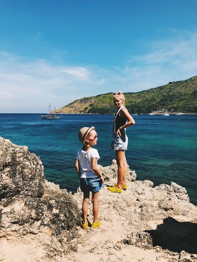 Full length of mother and daughter standing on rock formation at beach against sky