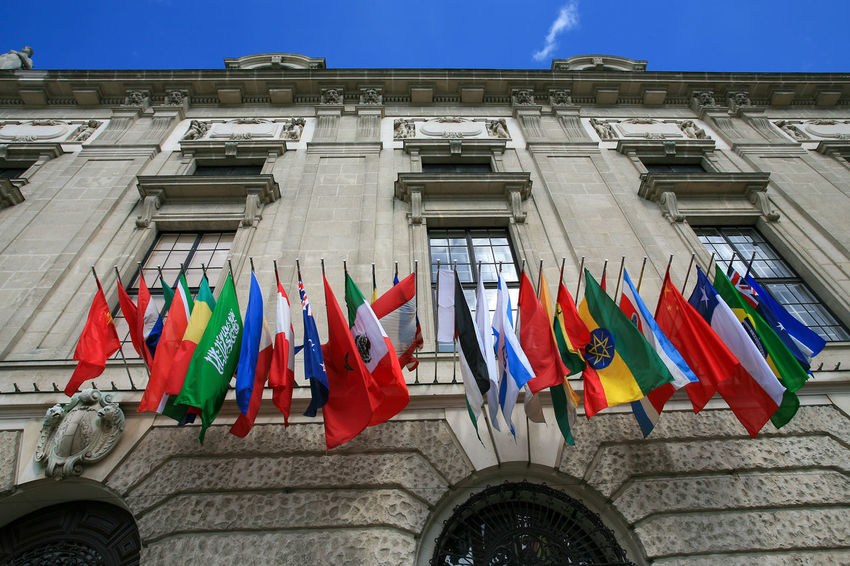 Many flags of the world on the facade of a historic building City Country International Travel Vienna Architecture Building Building Exterior Flag Hanging Historic In A Row Looking Up Low Angle View Multi Colored Nation No People Organization Outdoors Patriotism Sky Symbol United Window World