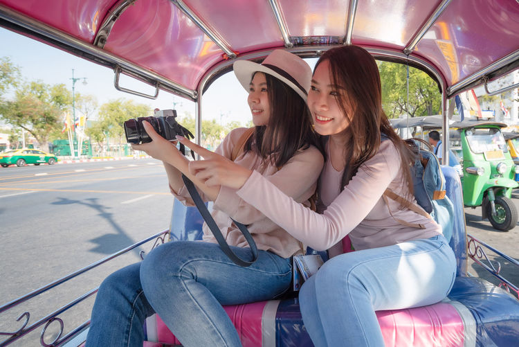Young woman photographing with mobile phone sitting in bus