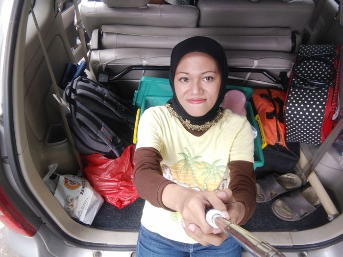 High angle portrait of young woman leaning on car trunk