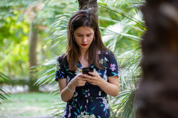 Young woman using mobile phone while standing on tree