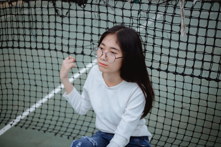 Young woman sitting against tennis net