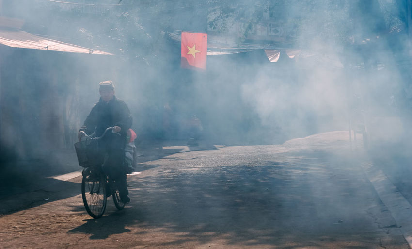 Mature man riding bicycle on road with smoke