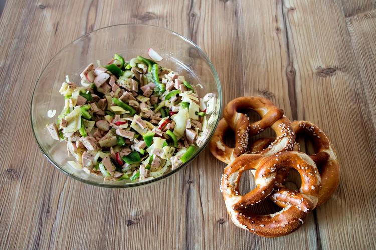 High angle view of pretzel and salad on table