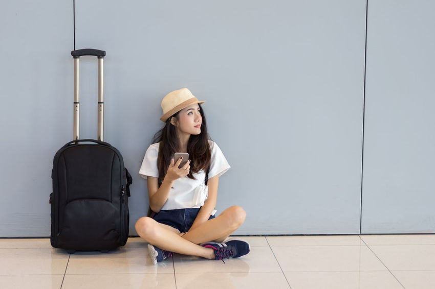 Asian woman teenager using smartphone at airport terminal sitting with luggage suitcase and backpack for travel in vacation summer relaxing waiting flight transport online check in or booking ticket Asian  Check-in Passenger Tourist Travel Waiting Woman Airport Backpack Baggage Female Flight Girl Internet Addict Journey Lifestyles Luggage Online  People Smartphone Summer Terminal Tourism Traveler Young Adult