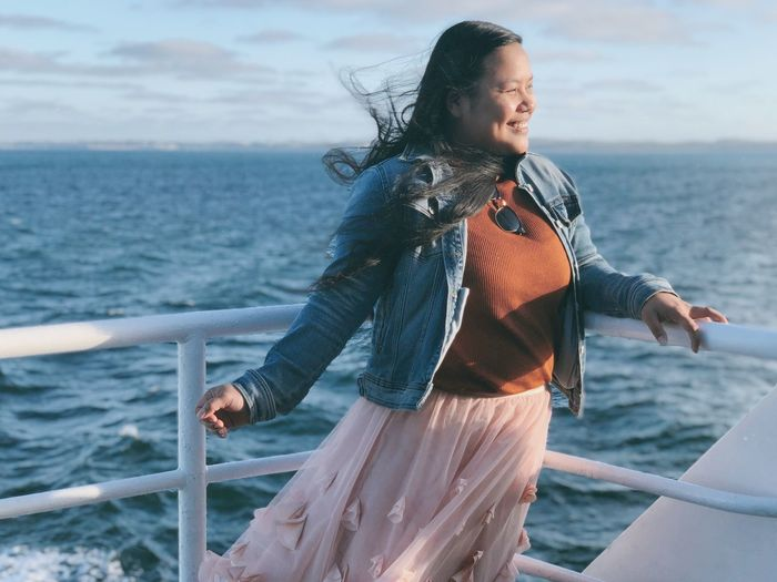 Smiling woman standing by railing against sea
