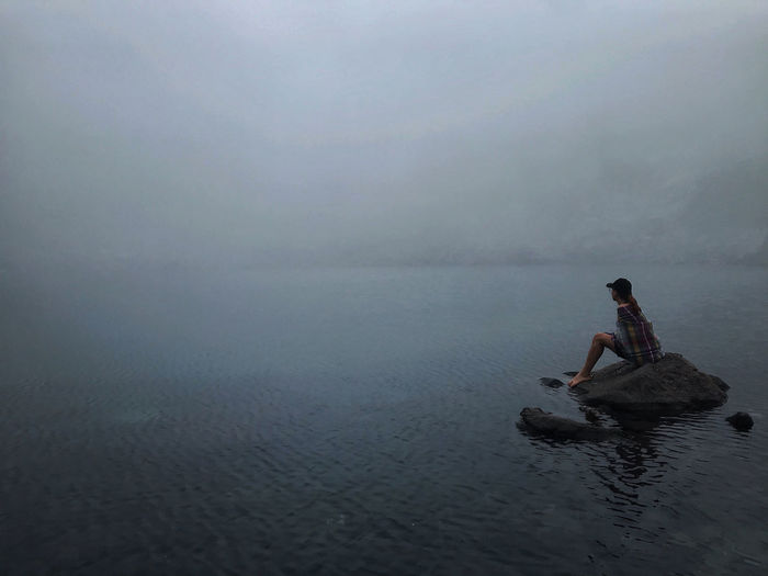 Side view of woman sitting on rock in lake during foggy weather