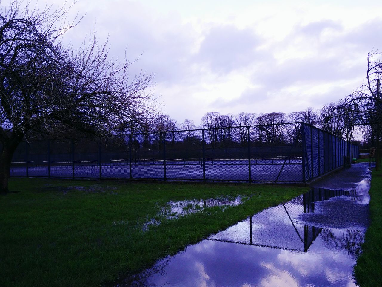 Puddle On Footpath By Playing Field Against Sky
