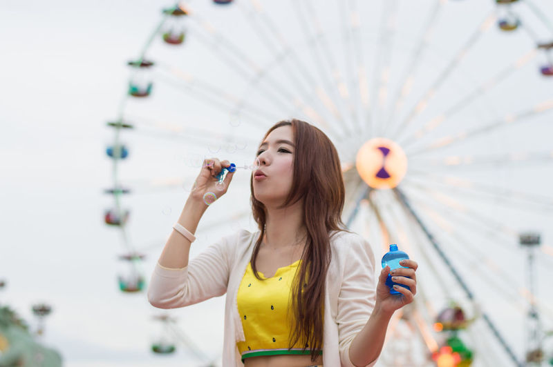 Young woman blowing bubbles while standing in amusement park