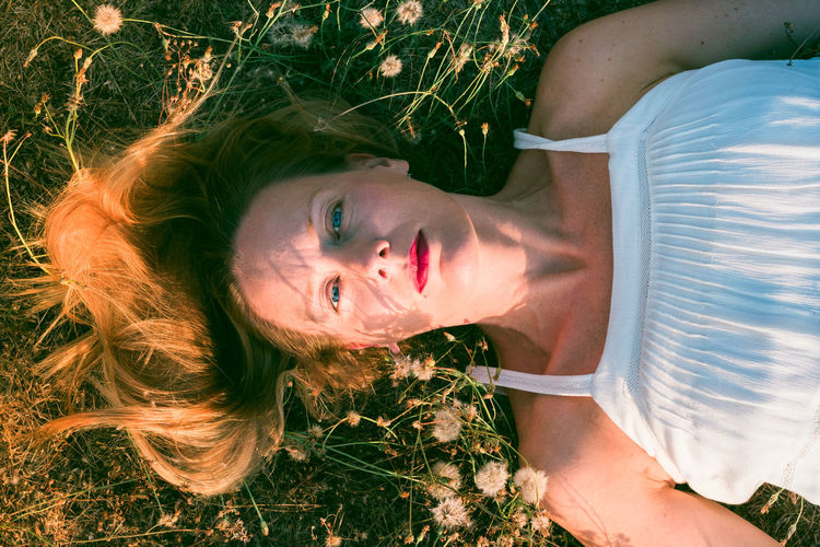 High Angle Portrait Of Woman Lying Down On Field