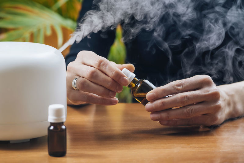Aromatherapy essential oil home diffuser. adding natural aromatic essential oil into air humidifier