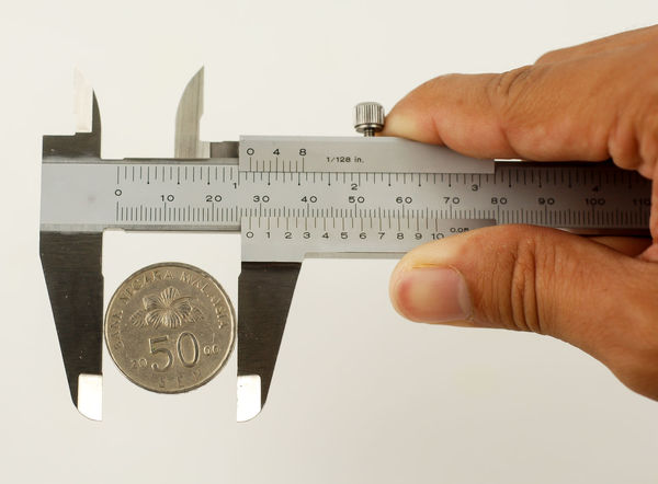 A hand hold vernier caliper with a coin as a concept of cost for quality Quality Audit Close-up Complaint Cost Customer  Day Defect Engineering Financial Focus Human Body Part Human Hand Instrument Of Measurement Measure Number One Person Precision Real People Studio Shot Vernier Caliper White Background