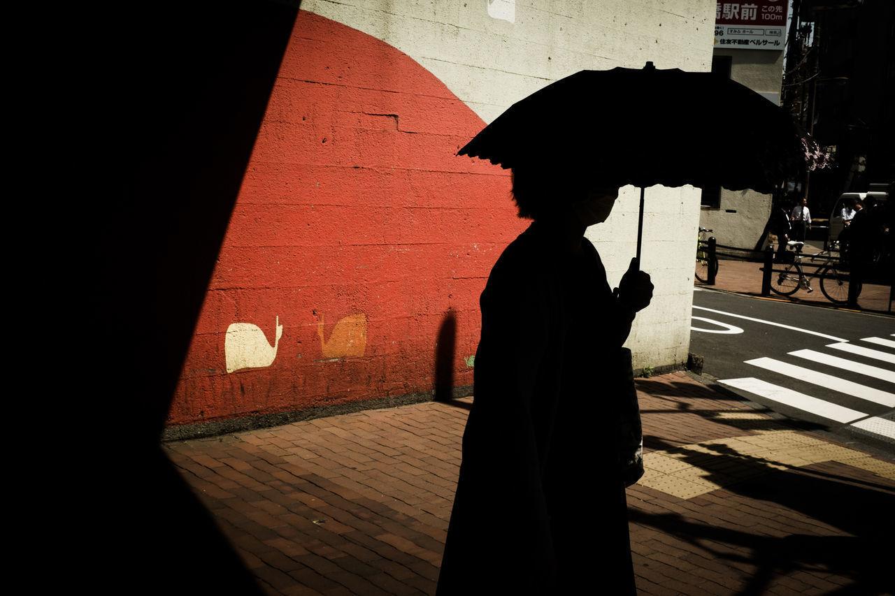 SILHOUETTE WOMAN WALKING ON FOOTPATH IN RAIN
