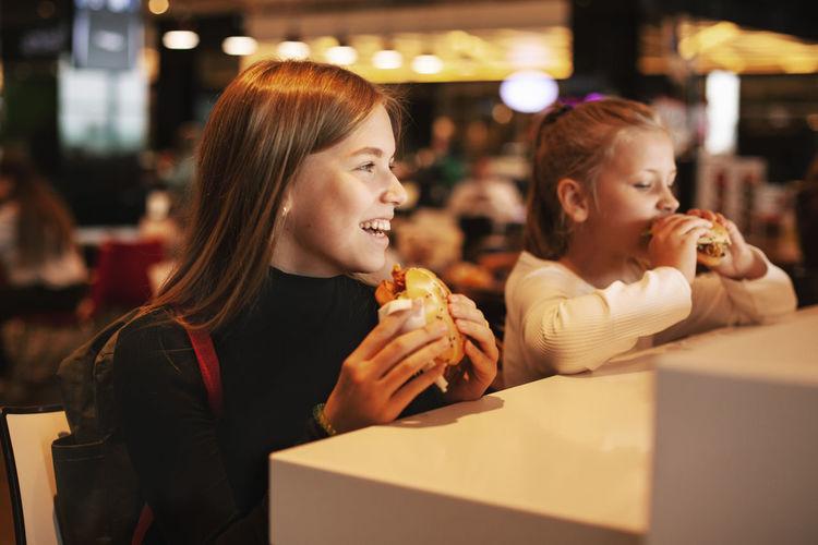 Beautiful schoolgirl eating hamburger sitting in a cafe indoors. happy child eating junk food