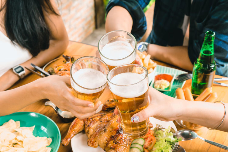 Drink Refreshment Real People Alcohol Food And Drink Beer - Alcohol Beer Group Of People Lifestyles Human Hand Table Togetherness Adult Women Friendship Leisure Activity Celebratory Toast Human Body Part Hand Holding Glass Beer Glass Frothy Drink